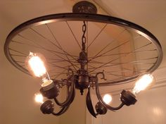 We created this bike rim chandelier from the rear wheel of an old bike. (24 diameter) It also includes various vintage light fixtures and lamp