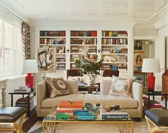 Room of the Day ~ Glass top, gold trim coffee table, interesting combination of furniture, red lamps, pillow print, love those dark chairs - NY living room of Philip Gorrivan
