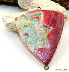 This beautiful pendant would make a wonderful focal element in your jewelry design! I handmade this pendant using my new favorite technique faux ceramics. A crackle medium was applied, aged and then sealed. This polymer clay technique creates a pendant that is so realistic to a true ceramic that you will fool most people. The advantage to polymer clay is that it is lightweight and will not break, unlike ceramic or stoneware.  This beautiful pendant is 48mm long and 44mm wide (at its widest…