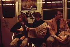 A woman reading the New York Post on the subway. | 32 Revealing Photos Of New York City In The 1970s
