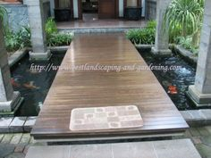 Koi pond with structured shape and a bridge over it.