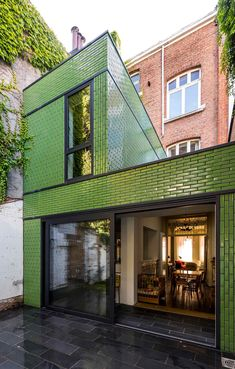 The town house in Zurenborg, Belgium consists of traditional brick; the rear extension is covered in the same material but thanks to its glazing shines in bright green. It matches well with the green garden scenery in the back yard. Single-family house in Brick Cladding, House Cladding, Brick Facade, Exterior Cladding, Facade House, Brickwork, Colour Architecture, Brick Architecture, Exterior Tiles