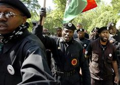 New Black Panther Party members march toward the gates of Duke University as they surround their leader, Malik Z. Shabazz (Back-C) May 1, 2006 in Durham, North Carolina.