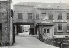 De brug naar de hoofdingang van de machinefabriek Breda ( Backer en Rueb) aan de Nieuweweg, gezien vanuit de richting van de Waterstraat.   Door de poort gekeken zien we op de achtergrond een deel van de Seeligkazerne.  De foto dateert tussen 1935-1940. Fotograaf: niet bekend.