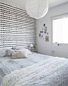 Dekologia Design -nettikaupasta tilattu Ferm Livingin Half Moon -tapetti koristaa makuuhuoneen seinää. Riisipaperivalaisin ja Ofelia-torkkupeitto ovat Ikeasta. Pellavapussilakanat ja -tyynyliinat ovat Annon mallistoa. Koristetyynyt ovat Ikeasta, Kodin Ykkösestä ja Askosta. Lukuvalaisimen jalka on Marimekosta, varjostin Ylhäisten sisustustehtaalta.