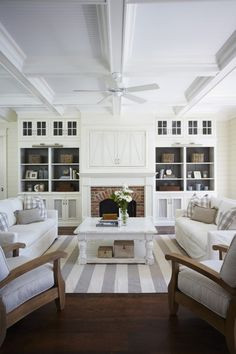 white and wood family room love the pillows and the concealed TV and built ins