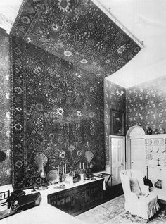 Kelmscott House dining room decorated with a Persian carpet hung on the wall (photograph taken in the late 1890s) with william morris's Pimpernell patterned wallpaper