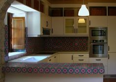 Love the use of bright patterned tiles in this otherwise plain kitchen.