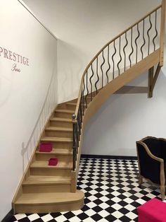 """Escalier bois quart tournant en bois de la gamme prestige """"PARIS"""". Marche de départ arrondie et poteau de départ en fer forgé. Le garde-corps le long de l'escalier est composé de balustres ondulées en fer forgé brut."""