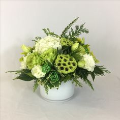A green and white holiday floral arrangement featuring green roses, hydrangeas, cedar, Princess Pine, lotus pods and wire balls.