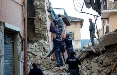 A woman is helped to leave his home by rescuers following a quake in Amatrice…