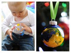 """mettez de la peinture dans une boule en acrylique, fermez hermétiquement et... laissez les enfants jouer avec ! résultat ? des boules marbrées qui feront de jolis souvenirs ! d'autant plus que la scrappeuse (qui ne sommeille pas une seule seconde) en moi vous conseille d'immortaliser la scène : de jolies boules ET une page de scrap, allez, hop ! à défaut d'enfant, faites jouer Toutou ou Matou avec ces jolies """"baballes"""" ! (espérons qu'il ne voudra pas les récupérer une fois dans le sapin...)"""