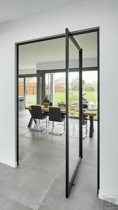"Glass pivot door with invisible pivoting hinges. The black anodized frame creates a ""steel look"". Pivot Doors, Modern Interiors, Glass Doors, Design Awards, Black Metal, Custom Made, New Homes, House Design, Windows"