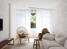 sala-sofa-tv-janela-branco-neutro-tijolos-aparentes-cortina-poltrona (Foto: Djan Chu/Divulgação)