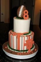 Two tier University of Texas theme cake with football on top.JPG