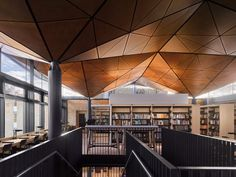 Woods Bagot has completed a library building at a girls' boarding school in Wiltshire, England, that features a faceted wooden ceiling designed to evoke spreading tree branches.