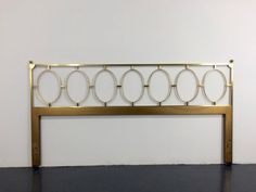 Totally glamorous vintage king size brass headboard on wooden frame. Seven oval brass rings juxtapose against a linear frame of solid brass