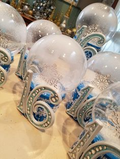 I used acrylic light covers and boxes from the dollar store to create these snowglobe centerpieces. A little sprinkle snow and spray snow added the final touch! I added some snowflake and small silver tinsel to add that winter Wonderland touch.