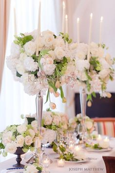 Silver candelabra with mound of cream hydrangea, blush spray roses, dusty miller, and dripping seeded eucalyptus.  The candelabras we use will have hurricanes around the taper candles