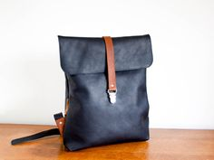 Leather backpack with strap closure. Custom designed and handmade by Sas de Vries