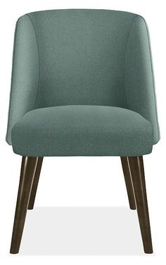 Sit with family and friends for as long as you like—the extreme comfort of our Cora chair invites you to linger at the table. The soft curves of the wraparound back highlight the thin tapered legs and welted fabric.
