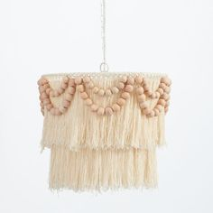 A little bit beachy, a little bit boho-chic, this handmade chandelier has tiers of cotton fringe accented with garlands of wooden beads. DETAILS YOU'LL APPRECIATE Handmade Chandelier, Wood Bead Chandelier, Pendant Lighting Bedroom, Floral Chandelier, Chandelier Bedroom, Chandelier Lighting, Chandelier Ideas, White Chandelier, Bedroom Decor