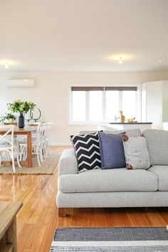 Lounge room, living room, open plan kitchen and living room, contemporary styling, large sofa, neutral colour palette, woollen floor rug, polished floorboards