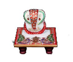 This peacock chowki with Ganeshji is a must have for daily worship. It can be kept in puja room or displayed as exquisite home decor. The white marble hand painted item has red, golden and blue designs with kundan work.