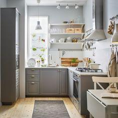 Kisméretű, hagyományos stílusú szürke és fehér konyha, BODBYN fiókelőlapokkal szürke színben és sárgaréz színű ENERYDA fogantyúk.