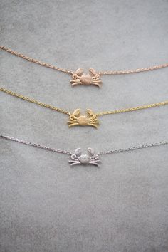 A maryland blue crab necklace in gold, rose gold, and silver.
