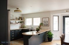 Dark kitchen cabinets, white tile, open shelves and brass! Come over to see this DIY kitchen !!