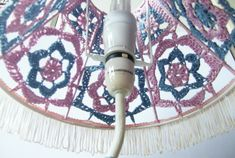 The lamp is unique and one of a kind. The lampshade is made of lacy hand-crocheted patterns, sewn to the frame. The colors, and forms carefully assorted to create an effect of vintage charm and Innocence, while the stand and base lend the product a more quirky and modern feel.