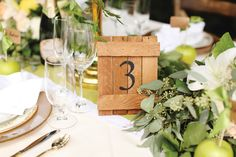 """Table number """"fences"""" create an easy-going farm table feel, as do the green apple name cards. PHOTOS BY VINE & LIGHT PHOTOGRAPHY Rustic Romance - Orlando Magazine - June 2015 - Orlando, FL"""