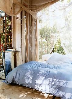 bedroom in blue with fabric draping on the walls