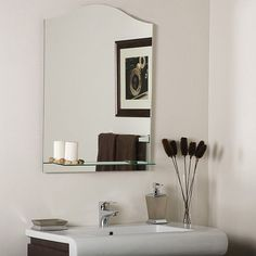 Great for bathrooms or a hallway, this frameless mirror is crafted from a strong, thick glass and has a double coated silver backing with seemed edges. This mirror features a convenient shelf and a modern style.