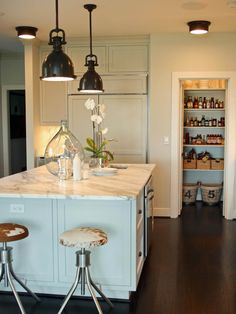 Industrial style lighting, marble counter, pastel island and love the cowhide print stools. Nice mix.