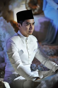 Traditional Malay groom attire with black Songkok hat // Malaysian TV personalities Amar Baharin and Amyra Rosli tied the knot in a lavish nikah (solemnisation ceremony) in Kuala Lumpur, Malaysia. The bride wore a jaw-dropping bespoke blush ball gown made of French lace and Swarovski crystals, while the groom looked every part the knight in shining armour in his Prince Charming-inspired suit by Rizman Ruzaini Creations. Here, we take you inside this celebrity couple's fairytale come to life…