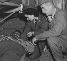 A C-47 air evacuation team from the 803rd Medical Air Evacuation Transportation Squadron, Lt. Pauline Curry and Tech. Sgt. Lewis Marker, check a patient on a flight over India. (U.S. Air Force photo)