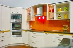 Idea of the Day: Modern Cream-Colored Kitchen with orange glass backsplash.