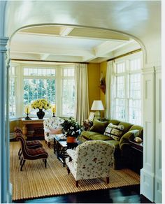 So much to like here: green couch, floral chairs, tufting, dark floors, coffered ceiling, lacquer, archway, windows...