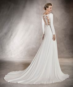 This is the perfect marriage between simplicity and fantasy! Its bateau neckline, with it's back in thread embroidery and gemstones is perfect for any elegant wedding! @Pronovias
