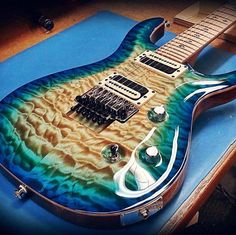 Check this gorgeous solid body from Carvin Custom Shop USA, featuring a quilted maple top with triple step colors in a Deep Lizardburst finish that depicts the ocean and a sandy island, twin Classic Series C22B and C22J humbuckers with exposed black and cream coils, and M bridge - Floyd Rose tune-o-matic bridge set in body with strings fed through.