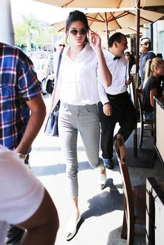 Kendall Jenner in a white button-up shirt, striped jeans, white sneakers, and aviators