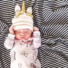 Cute baby in a pink unicorn baby grow and hat with unicorn hat attached