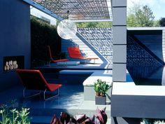 An intricate lattice roof is used to cast a dramatic shadow in this modern backyard. Strong geometric shapes and bold colors create a space that is signature of modern, outdoor design.