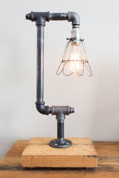 Industrial Pipe Lamp Industrial, custom table lamp or desk lamp made from steel gas pipe fittings. The lamp is mounted to a piece of 2 inch cedar