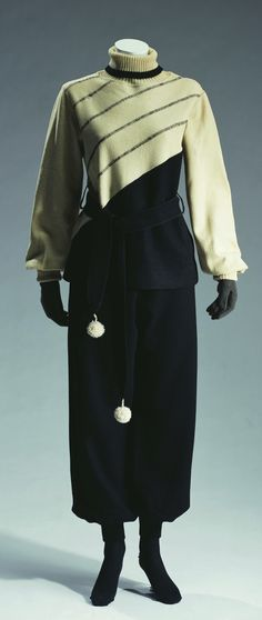 Ski suit, c. 1930. Set of black and off-white wool sweater and black wool knit pants; rib-knit turtleneck and cuffs; matching belt with pom-poms at ends. ©The Kyoto Costume Institute, photo by Takashi Hatakeyama.