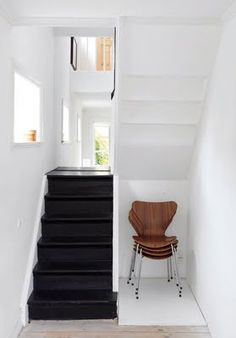 White walls highlight the black staircase. The chairs, instead of appearing to be just randomly shoved into a nook, appear to be showcased like an art piece instead due to the minimalism and white surroundings.