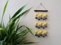 Amazing pompon wall hanging with handmade acrylic pompons hanging by a cotton cord. Length 21.26 (54 cm). Width of wooden stick (oak) 8.66 (22 cm). Diameter of pompons 1.57 (4cm).