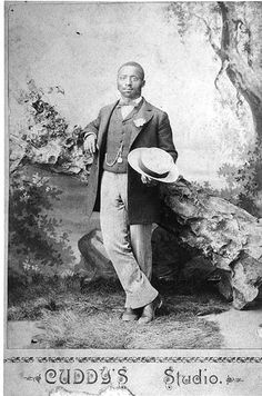 African American man standing in long coat, striped trousers, holding a straw hat. c.1890
